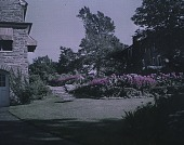 view [Unidentified Garden in Unidentified Location]: stone house with path, steps, and pink flower border. digital asset: [Unidentified Garden in Unidentified Location] [lantern slide]: stone house with path, steps, and pink flower border.