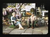 view [The Chimneys]: man and woman sitting on patio in lawn chairs. digital asset: [The Chimneys]: man and woman sitting on patio in lawn chairs.: 1940.