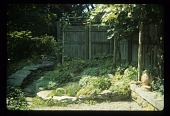 view [Mary's Garden]: the garden under the grape arbor with rocks edging. digital asset: [Mary's Garden] [slide (photograph)]: the garden under the grape arbor with rocks edging.