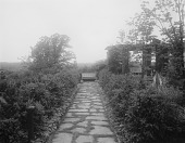 view [Edgewood (MD)]: stone walkway leading to a bench, with the end of the pergola on the right. digital asset: [Edgewood (MD)] [glass negative]: stone walkway leading to a bench, with the end of the pergola on the right.
