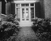 view [Holly Beach Farm]: a doorway with louvered shutters, after landscaping. digital asset: [Holly Beach Farm] [glass negative]: a doorway with louvered shutters, after landscaping.