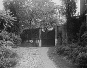 view [Holly Beach Farm]: a wooden gate between brick walls, with the house barely visible on the right. digital asset: [Holly Beach Farm] [glass negative]: a wooden gate between brick walls, with the house barely visible on the right.