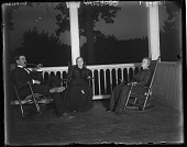view [White Garden]: two women and a man in rocking chairs on porch. digital asset: [White Garden] [glass negative]: two women and a man in rocking chairs on porch.