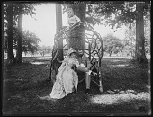 view [Tanglewood]: Mr. and Mrs. Hasson seated on a rustic work settee, with Oscar Liebig perched above them. digital asset: [Tanglewood] [glass negative]: Mr. and Mrs. Hasson seated on a rustic work settee, with Oscar Liebig perched above them.