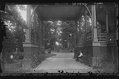 view [Tanglewood]: child sitting under the coach gate or carriage porch. digital asset: [Tanglewood] [glass negative]: child sitting under the coach gate or carriage porch.