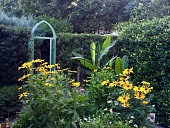view [Pappa's Patch]: the gothic style arched gate in the yew hedge leads to the Madonna garden room. A banana plant produces fruit. digital asset: [Pappa's Patch]: the gothic style arched gate in the yew hedge leads to the Madonna garden room. A banana plant produces fruit.