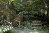 view [The Cottage Garden]: rustic work banister and stone stairs with wooden settee at lower level. digital asset: [The Cottage Garden]: rustic work banister and stone stairs with wooden settee at lower level.: 2004 Jul.