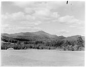 view [Miscellaneous Sites in the Adirondack Mountains]: looking across a field and woodlands, probably in the Lake Placid area, toward Whiteface Mountain in the distance, digital asset: [Miscellaneous Sites in the Adirondack Mountains] [glass negatives]: looking across a field and woodlands, probably in the Lake Placid area, toward Whiteface Mountain in the distance,