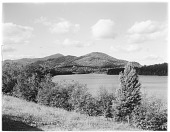 view [Miscellaneous Sites in the Adirondack Mountains]: Mirror Lake in Lake Placid, with the peak of Whiteface Mountain visible in the left center distance. digital asset: [Miscellaneous Sites in the Adirondack Mountains] [glass negative]: Mirror Lake in Lake Placid, with the peak of Whiteface Mountain visible in the left center distance.