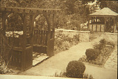 view [Rose Cove]: by the pergola in cutting garden looking down path and through the wall to the tea house in the rose garden. digital asset: [Rose Cove]: by the pergola in cutting garden looking down path and through the wall to the tea house in the rose garden.: [1925?]