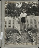 view [Breeze Hill]: woman in shorts with straw hat and hoe standing in front of gate to picket fence. digital asset: [Breeze Hill] [photographic print]: woman in shorts with straw hat and hoe standing in front of gate to picket fence.
