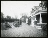 view [Schaeffer Garden: looking from the driveway through an arch or arbor toward the main garden, with the house on the right. digital asset: [Schaeffer Garden [lantern slide]: looking from the driveway through an arch or arbor toward the main garden, with the house on the right.