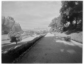view [Princes Street Gardens]: looking west along a garden walkway, with the bandstand and Edinburgh Castle in the left distance. digital asset: [Princes Street Gardens] [glass negative]: looking west along a garden walkway, with the bandstand and Edinburgh Castle in the left distance.