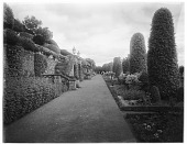 view [Drummond Castle]: a garden walkway along a terrace, with a stone retaining wall and stairs leading up to the castle. digital asset: [Drummond Castle] [glass negative]: a garden walkway along a terrace, with a stone retaining wall and stairs leading up to the castle.