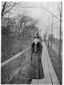 view [Miscellaneous Images]: an unidentified woman standing on a wooden walkway. digital asset: [Miscellaneous Images] [glass negative]: an unidentified woman standing on a wooden walkway.