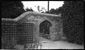 view [Unidentified Sites]: an unidentified arched opening in a latticed brick wall backing a garden border. digital asset: [Unidentified Sites] [negative]: an unidentified arched opening in a latticed brick wall backing a garden border.