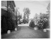 view [Unidentified Garden]: drive with brick house on left side. Four large stone blocks lining drive. digital asset: [Unidentified Garden] [photonegative]: drive with brick house on left side. Four large stone blocks lining drive.
