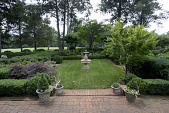 view [Periwinkle Cottage]: a garden room behind the house with a fountain centered in the lawn and trimmed boxwood hedges. digital asset: [Periwinkle Cottage]: a garden room behind the house with a fountain centered in the lawn and trimmed boxwood hedges.