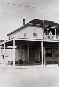 """view Stiglich Grocery, Mrs. Stiglich's father-in-law and mother-in-law on upper porch, 1932, from """"The Corner Stores of Galveston,"""" Galveston County Cultural Arts Council digital asset number 1"""