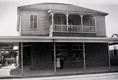 """view Stiglich Grocery, 2728 Avenue Q. Mrs. Stiglich and her father-in-law, 1936, from """"The Corner Stores of Galveston,"""" Galveston County Cultural Arts Council digital asset number 1"""