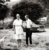 view Couple Holding a Portrait of Their Son (Standing in Front of the Car He Drowned In) Clay County, Kentucky, from the Kentucky Documentary Project digital asset number 1