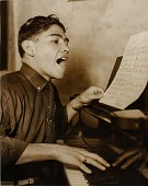 view Unidentified figure (boxer) singing at piano digital asset number 1