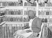 view Jorena Pettway sorting peas inside her smokehouse. She still has many fruits and vegetables, which she canned last year, on the shelves around her. Gee's Bend, Alabama digital asset number 1