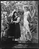 """view Marguerite Zorach standing in front of """"The Land and Development of New England"""" [photograph] / (photographed by Peter A. Juley & Son) digital asset number 1"""