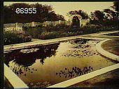 view [The Chimneys]: pond, with water lillies, surrounded by walkways. Flower beds along a fence with an arbor in background. digital asset: [The Chimneys]: pond, with water lillies, surrounded by walkways. Flower beds along a fence with an arbor in background.: [1930?]
