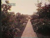 view [The Chimneys]: walkway through a garden with a variety of flowering plants and trees. An arbor is located at the end of the walkway. digital asset: [The Chimneys]: walkway through a garden with a variety of flowering plants and trees. An arbor is located at the end of the walkway.: [1930?]