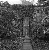 view [Baird Garden]: stone wall, trellis, and antique font. digital asset: [Baird Garden] [safety film negative]: stone wall, trellis, and antique font.