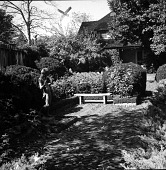view [Sargent, Lucy, Garden]: brick patio and sculpture, looking toward house. digital asset: [Sargent, Lucy, Garden] [contact print]: brick patio and sculpture, looking toward house.