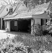 view [Unidentified Garden in Unknown Location]: Dutch Colonial style house and garage with climbing plant over top of garage door. digital asset: [Unidentified Garden in Unknown Location] [safety film negative]: Dutch Colonial style house and garage with climbing plant over top of garage door.