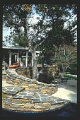 view [Untitled Garden in Pasadena, California]: curving stacked stone retaining walls with 'Bouquet Canyon' flagstone. digital asset: [Untitled Garden in Pasadena, California] [slide]: curving stacked stone retaining walls with 'Bouquet Canyon' flagstone.