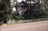 view [Hebert Family Home]: front of the Hebert house, showing latticed ivy, window boxes of impatiens, and pine trees. digital asset: [Hebert Family Home]: front of the Hebert house, showing latticed ivy, window boxes of impatiens, and pine trees.: 1999 Sep.