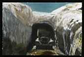 view [Canadian Rockies]: an automobile emerges from a snow tunnel in an unidentified location. digital asset: [Canadian Rockies]: an automobile emerges from a snow tunnel in an unidentified location.: [between 1915 and 1930]