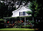 view [The Miller's House]: front view of house with containers on porch. digital asset: [The Miller's House]: front view of house with containers on porch.: 1998 Jul.