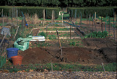 view [Community Gardens at Edgerton Park]: view of plots towards yew circle, showing peat moss bale, bins, and garden fork. digital asset: [Community Gardens at Edgerton Park]: view of plots towards yew circle, showing peat moss bale, bins, and garden fork.: 2001 Apr.
