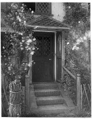 view [Miscellaneous Sites in Shere, Surrey, England, and Vicinity, Series 1]: a doorway flanked by climbing roses in an unidentified location. digital asset: [Miscellaneous Sites in Shere, Surrey, England, and Vicinity, Series 1] [glass negative]: a doorway flanked by climbing roses in an unidentified location.