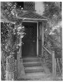 view [Miscellaneous Sites in Shere, Surrey, England, and Vicinity, Series 2]: a doorway flanked by climbing roses in an unidentified location. digital asset: [Miscellaneous Sites in Shere, Surrey, England, and Vicinity, Series 2] [glass negative]: a doorway flanked by climbing roses in an unidentified location.