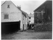 view [Miscellaneous Sites in Clovelly, Devon, England]: houses and walls, with a large boat on the left and a man coming down stairs. digital asset: [Miscellaneous Sites in Clovelly, Devon, England] [glass negative]: houses and walls, with a large boat on the left and a man coming down stairs.