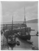 view [Miscellaneous Sites in Clovelly, Devon, England]: fishing boats and rowboats in the harbor alongside the quay. digital asset: [Miscellaneous Sites in Clovelly, Devon, England] [glass negative]: fishing boats and rowboats in the harbor alongside the quay.