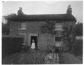 view [Miscellaneous Sites in Derbyshire, England]: Ann Hibbs in the doorway of her home in Rowsley. digital asset: [Miscellaneous Sites in Derbyshire, England] [glass negative]: Ann Hibbs in the doorway of her home in Rowsley.
