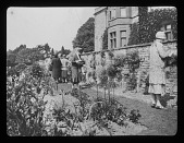 view [Abbotswood]: tour participants viewing flower beds and stone wall featuring cultivated plants. digital asset: [Abbotswood] [lantern slide]: tour participants viewing flower beds and stone wall featuring cultivated plants.