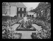 view [Abbotswood]: boxwood-hedged flower beds, with the house and its loggia in the background and the pergola on the right. digital asset: [Abbotswood] [lantern slide]: boxwood-hedged flower beds, with the house and its loggia in the background and the pergola on the right.