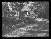 view [Sutton Courtenay Manor House]: garden area with brick path, brick wall, and distinctive posts in the background. digital asset: [Sutton Courtenay Manor House] [lantern slide]: garden area with brick path, brick wall, and distinctive posts in the background.