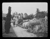 view [Orchard Farm]: Garden Club of America tour participants admiring a garden border tumbling over a stone wall. digital asset: [Orchard Farm] [lantern slide]: Garden Club of America tour participants admiring a garden border tumbling over a stone wall.