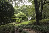 view [Haskell Gardens]: Charles Perry's 'Ribbed Mace' is backed by specimen hollies. digital asset: [Haskell Gardens]: Charles Perry's 'Ribbed Mace' is backed by specimen hollies.: 2009 May