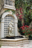 view [Villa Filipponi]: a flowering Tecomanthe vine and potted bougainvillea decorate a tiled fountain with satyr sculpture. digital asset: [Villa Filipponi]: a flowering Tecomanthe vine and potted bougainvillea decorate a tiled fountain with satyr sculpture.: 2013 Apr.