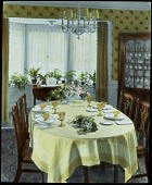 view [Miscellaneous Flower Arrangements]: flower and fruit arrangments on a dining table. digital asset: [Miscellaneous Flower Arrangements]: flower and fruit arrangments on a dining table.: [between 1914 and 1949?]